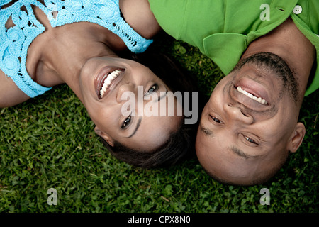 Closeup portrait of a young black couple, lying on the ground, smiling at the camera - Stock Photo