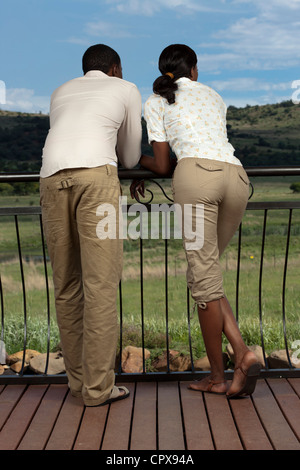 An African couple enjoy the scenery from a deck over-looking a Game Reserve - Stock Photo
