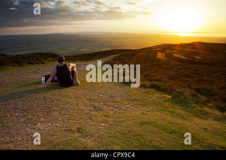 A fell runner resting on top of Moal Famau the highest point in the Clwydian Range Hills as the sun sets over the - Stock Photo