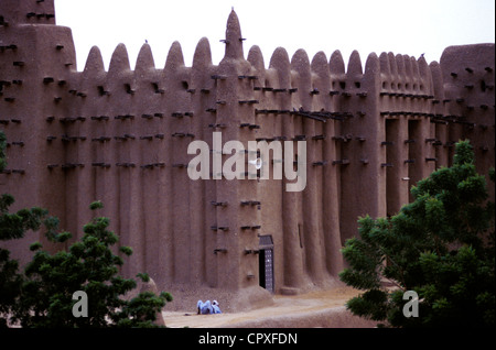 Mali Mopti Region Djenne listed as World Heritage by UNESCO a man resting under Great Mosque (biggest mud brick - Stock Photo