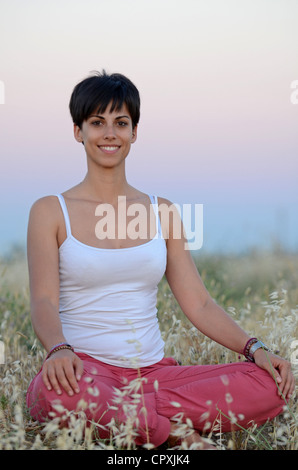 Attractive short haired woman practices yoga in nature - Stock Photo