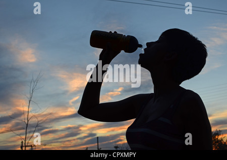 Young woman drinks water after bike ride - Stock Photo