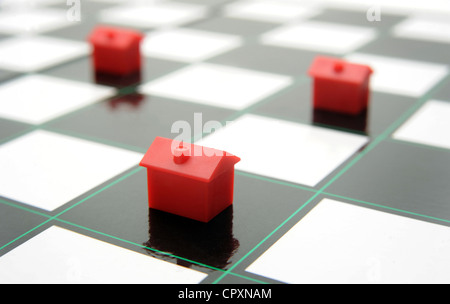 MODEL HOUSES ON CHESSBOARD RE MOVING HOUSE PROPERTY MARKET BUYING SELLING HOUSING PRICES COSTS BUDGETS HOUSEHOLD - Stock Photo