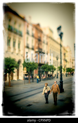 A couple walking along a street in Spain - Stock Photo