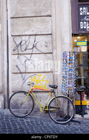 Yellow bike parked Old yellow bike parked against a rack containing postcards in Rome. - Stock Photo