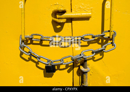 padlocked and chained steel door on a skip - Stock Photo