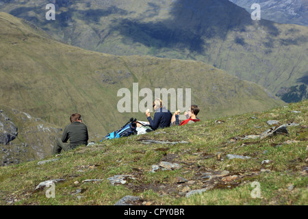 Girls sitting down enjoying lunch on the slopes of Sgurr an Doire Leathain the fifth Munro top on the South Glen - Stock Photo