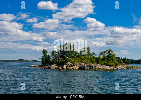 Red cottage on a small rocky island in Stockholm archipelago - Stock Photo