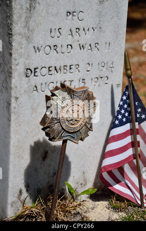 World War II veteran's graved adorned with U.S. flag and VFW marker - Stock Photo