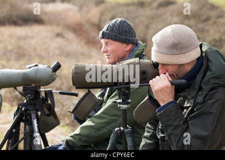 bird watchers with telescope on tripod in winter - Stock Photo