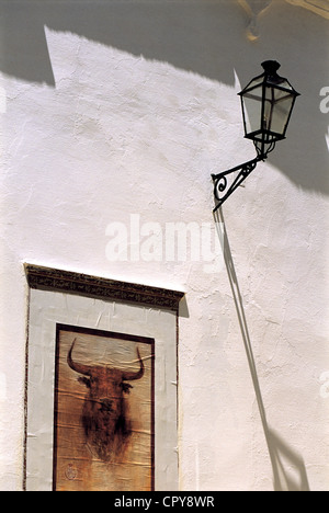 Spain, Andalucia, Sevilla, Plaza de Toros La Maestranza, Ad for a corrida and street lamp on a white wall - Stock Photo
