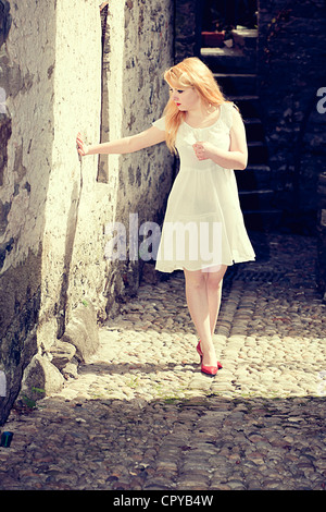 young woman in white dress standing in a narrow alley