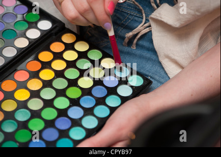 A young woman choosing the correct colour make up for a make-over session at a salon UK - Stock Photo