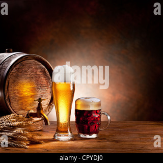 Beer barrel with beer glasses on a wooden table. The dark background. - Stock Photo