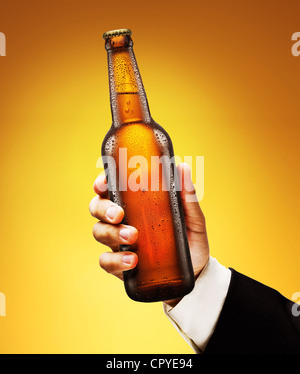 Bottle of beer in a man's hand on a yellow background. - Stock Photo