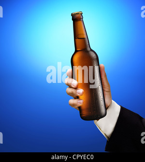 Bottle of beer in a man's hand on a blue background. - Stock Photo