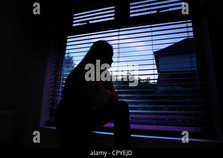 Young female sitting alone in a dark room looking out through a window blind. - Stock Photo