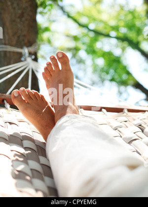 Feets in a hammock on a summer nature background. - Stock Photo