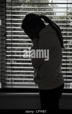 Profile of a girl with a ponytail, hands covering her face. Silhouette. - Stock Photo