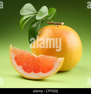 grapefruit with leaves on a green background - Stock Photo