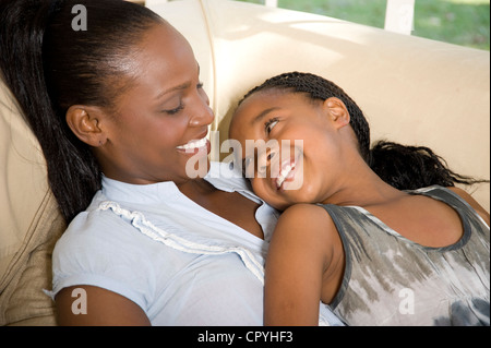 Young African mother lying with her daughter on a couch - Stock Photo