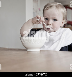 Young boy (15 months) eating yoghurt on his own with a spoon, wearing bibs - Stock Photo