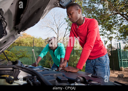 Two African men working on a car engine - Stock Photo