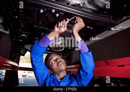 African mechanic standing under a car, working on the engine - Stock Photo
