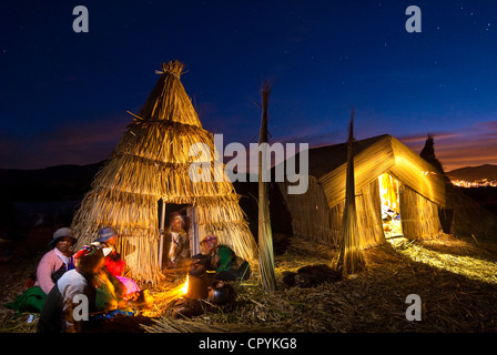Peru, Puno Province, Titicaca lake, floating islands of Uros, evening family meal at home heated with dried reed - Stock Photo