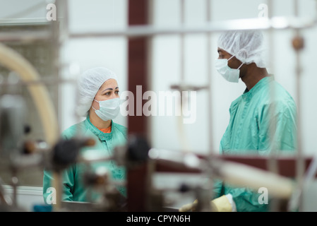 Laboratory technicians at work in medical plant with machinery and computers - Stock Photo