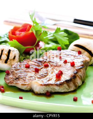 Pork steak with mushrooms and tomato rose on white background - Stock Photo