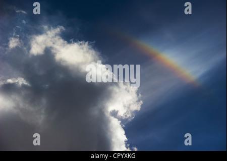 Rainbow against cloudy sky - Stock Photo