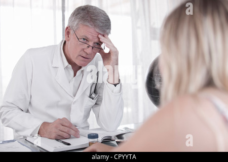 Doctor talking to patient in office - Stock Photo