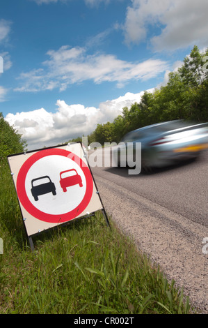 car passing no overtaking warning sign due to loose chippings on newly resurfaced road uk - Stock Photo