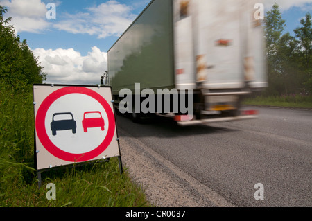lorry passing no overtaking warning sign due to loose chippings on newly resurfaced road uk - Stock Photo