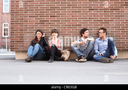 Friends relaxing on city street - Stock Photo