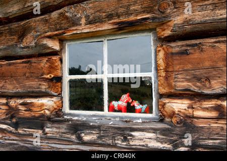 Red Dalarna horses displayed in a window, old log cabin, Valdalsbygget near Groevelsjoen, Dalarna province, Sweden, - Stock Photo