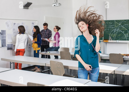 Student dancing to mp3 player in class - Stock Photo