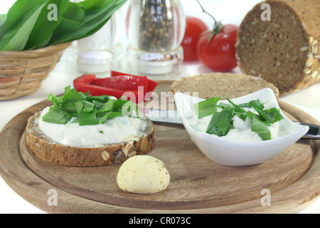 a slice of bread with cottage cheese and freshly chopped wild garlic - Stock Photo