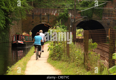 a view of a bridge with two arches - one crossing a railway and the other crossing a canal in Birmingham - cyclists - Stock Photo