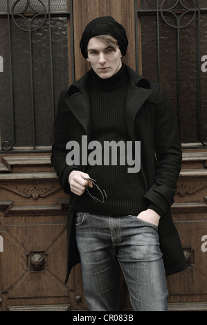 Young man wearing winter clothes, standing in front of a front door - Stock Photo