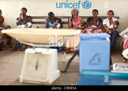 Women wait to have their children vaccinated during a routine follow-up visit at the Henriette Konan Bedie Community - Stock Photo