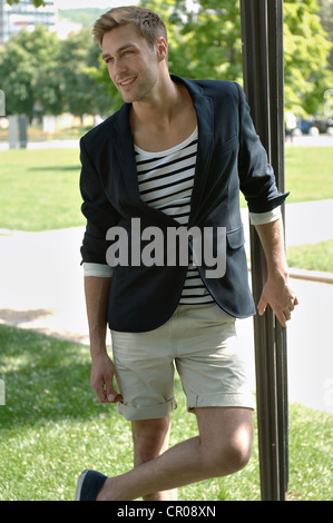 Young man in casual outfit leaning on a lamppost in a summerly park - Stock Photo