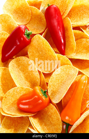 Oval paprika potato chips, stacking chips, with sweet peppers, full-frame - Stock Photo