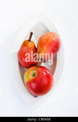 Red apple and two red pears on a plate - Stock Photo
