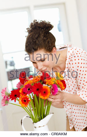 Woman smelling bouquet of flowers - Stock Photo