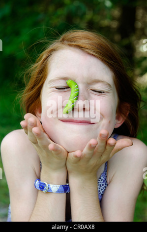 Girl with a huge caterpillar on her face - Stock Photo