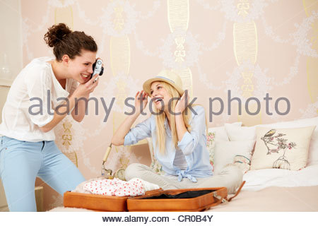 Women packing suitcase in bedroom - Stock Photo