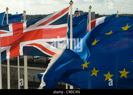 Union Jack and European Union flags flying on numerous flag poles - Stock Photo