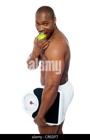 Young man enjoying fresh green apple and holding weighing scale in one hand - Stock Photo
